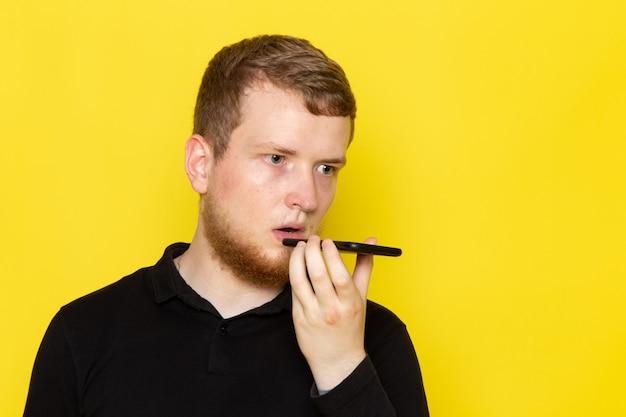 Vista frontale del giovane in camicia nera, parlando al telefono