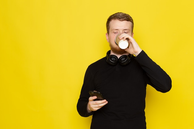Front view of young man in black shirt using phone and drinking coffee