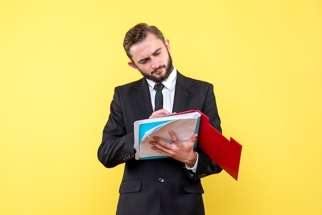 Vista frontale del giovane in abito nero cheking appunti rossi con cartella blu su giallo