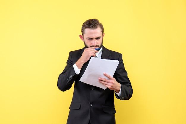 Vista frontale del giovane in abito nero, concentrandosi sul documento vuoto sulla parete gialla