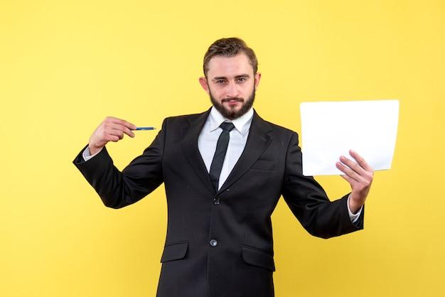 Vista frontale del giovane in abito nero che punta con sicurezza con una penna sul documento in bianco su giallo