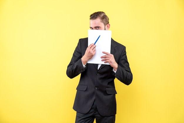 Front view of young man in black suit hiding lower part of face and pointing with a pen on blank document on yellow
