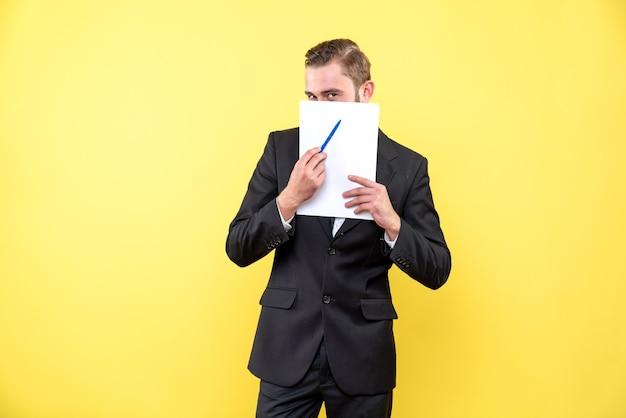Vista frontale del giovane in abito nero che nasconde la parte inferiore del viso e indica con una penna sul documento in bianco su giallo