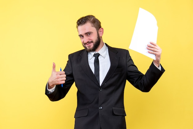 Front view of young man in black suit holding blank paper over yellow with smile thumb up with fingers excellent sign