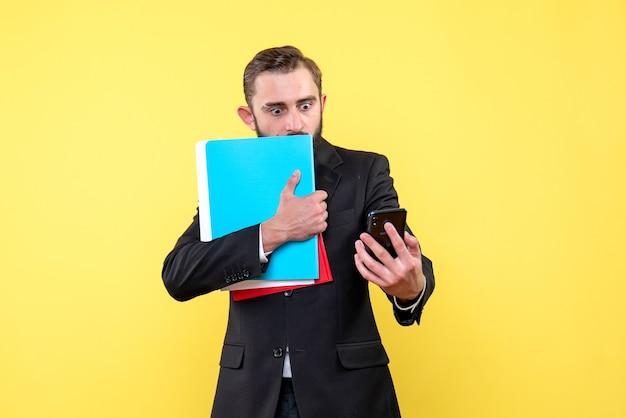 Vista frontale del giovane in vestito nero che tiene le cartelle e guardando spaventato un telefono in giallo