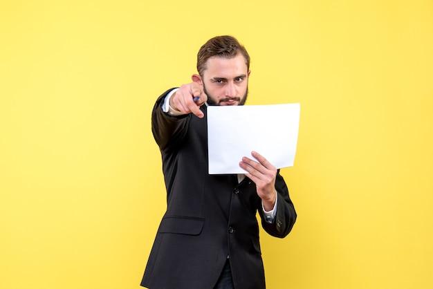 Vista frontale del giovane in vestito nero che osserva e che indica rigorosamente con una penna che tiene un documento in bianco su colore giallo