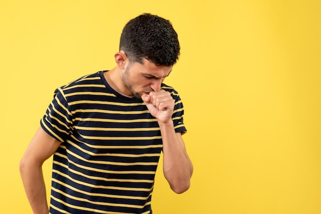 Front view young man in black and white striped t-shirt coughing on yellow isolated background