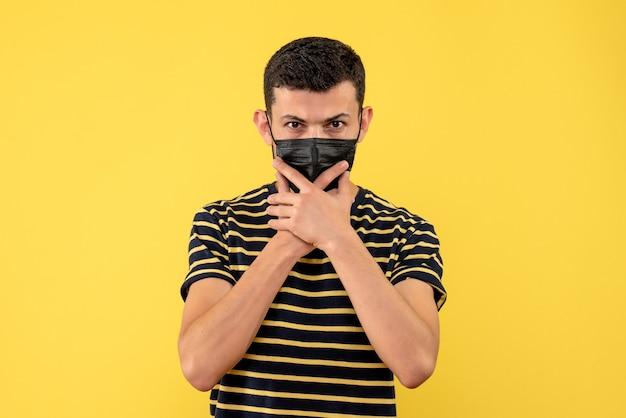 Giovane di vista frontale in maglietta a strisce in bianco e nero che tiene fondo isolato giallo del mento