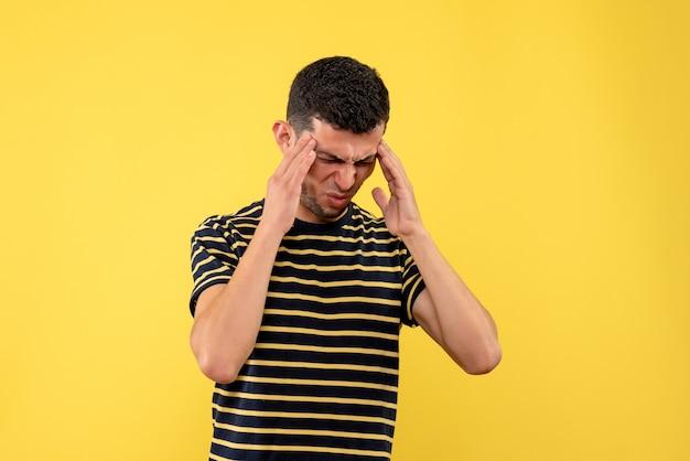 Giovane di vista frontale in maglietta a strisce in bianco e nero che tiene la testa con dolore su sfondo giallo isolato