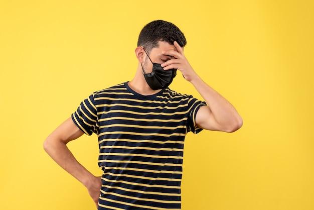 Giovane di vista frontale in maglietta a strisce in bianco e nero che tiene il fondo giallo della testa