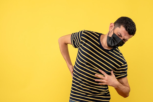 Front view young man in black and white striped t-shirt holding his back with pain on yellow background