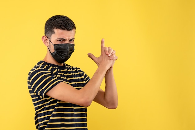 Front view young man in black and white striped t-shirt making finger gun on yellow background