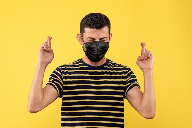 Giovane di vista frontale in maglietta a strisce in bianco e nero che fa il fondo giallo del segno di buona fortuna