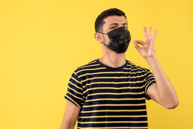 Giovane di vista frontale in maglietta a strisce in bianco e nero che fa priorità bassa gialla del segno giusto