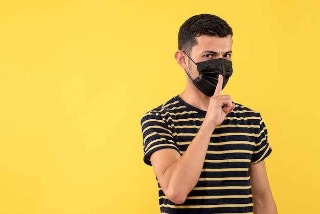 Giovane di vista frontale in maglietta a strisce in bianco e nero che fa segno di shh su priorità bassa gialla