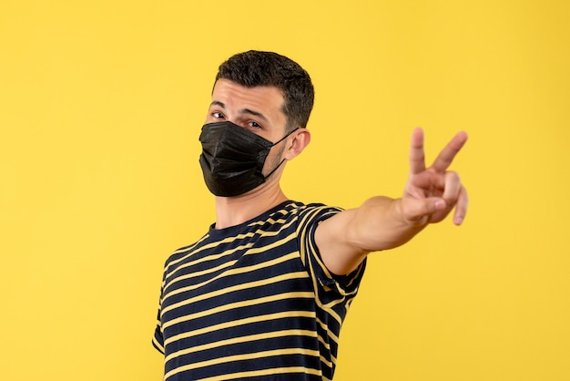 Front view young man in black and white striped t-shirt making victory sign yellow background