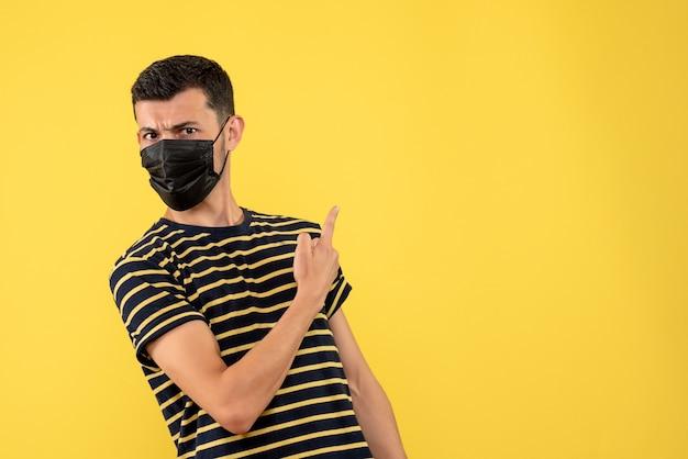 Giovane di vista frontale in maglietta a strisce in bianco e nero che indica indietro su priorità bassa gialla