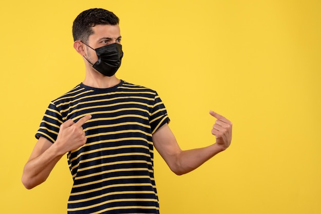 Front view young man in black and white striped t-shirt pointing at himself yellow background