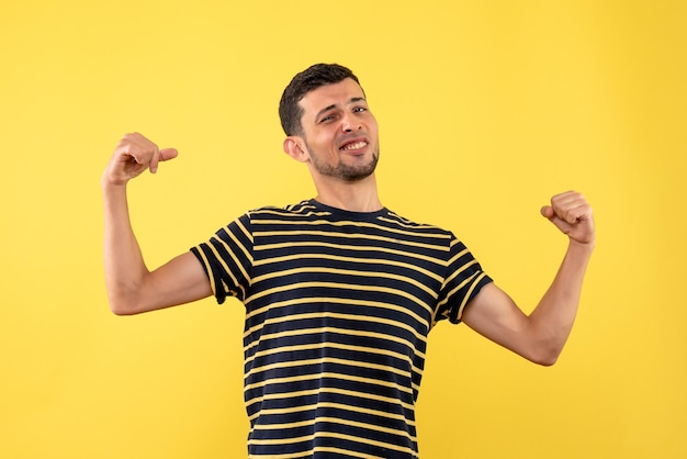 Front view young man in black and white striped t-shirt pointing at himself on yellow isolated background