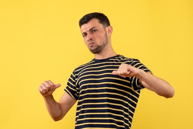 Giovane di vista frontale in maglietta a strisce in bianco e nero che indica a se stesso fondo isolato giallo