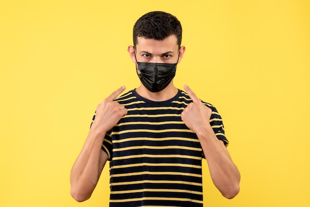 Front view young man in black and white striped t-shirt pointing at his mask on yellow isolated background
