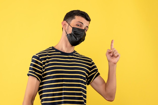 Front view young man in black and white striped t-shirt pointing with finger up on yellow isolated background