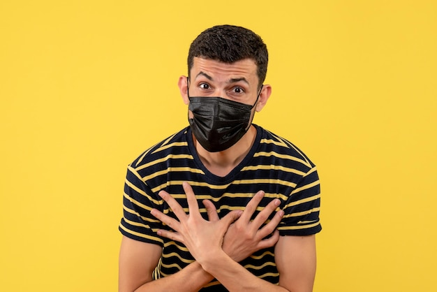 Front view young man in black and white striped t-shirt putting hands on chest on yellow isolated background