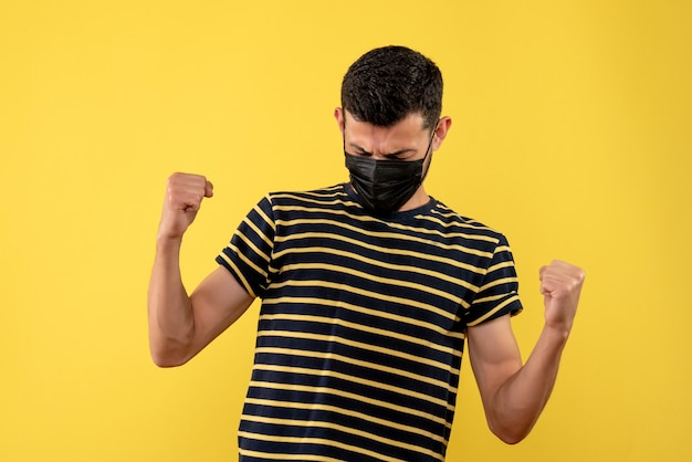 Giovane di vista frontale in maglietta a strisce in bianco e nero che mostra il gesto vincente su priorità bassa gialla