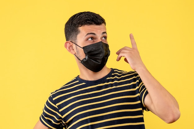 Front view young man in black and white striped t-shirt standing on yellow background