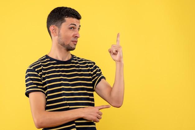 Giovane di vista frontale in maglietta a strisce in bianco e nero che sta su fondo isolato giallo