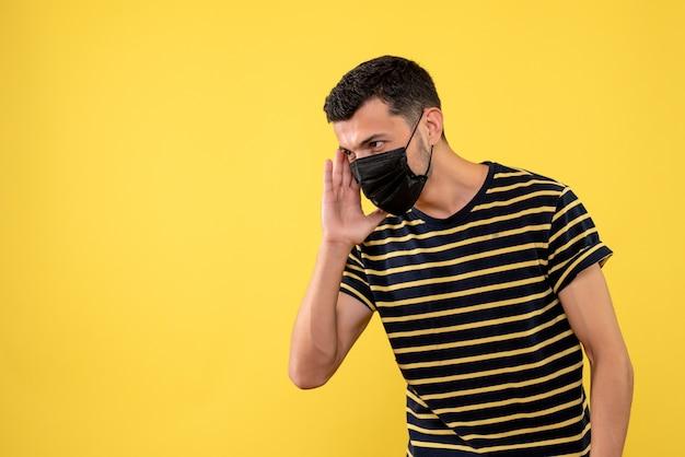 Giovane di vista frontale nello spazio della copia del fondo giallo della maglietta a strisce in bianco e nero