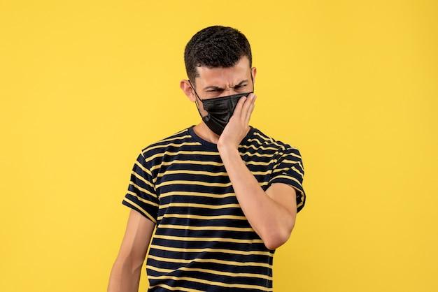 Giovane di vista frontale nella priorità bassa gialla della maglietta a strisce in bianco e nero