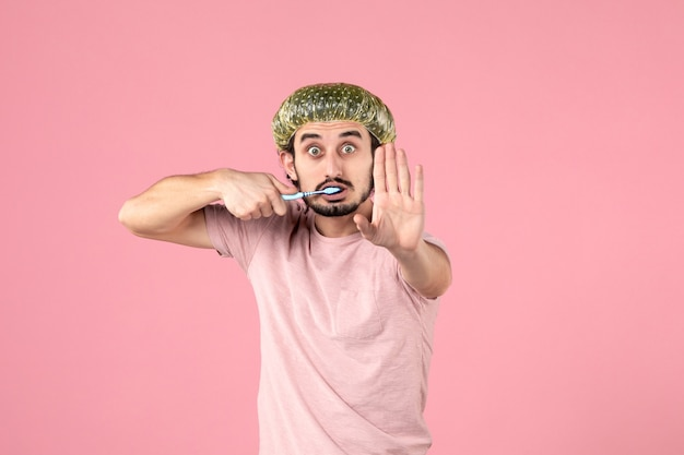 Front view of young man brushing his teeth on pink wall