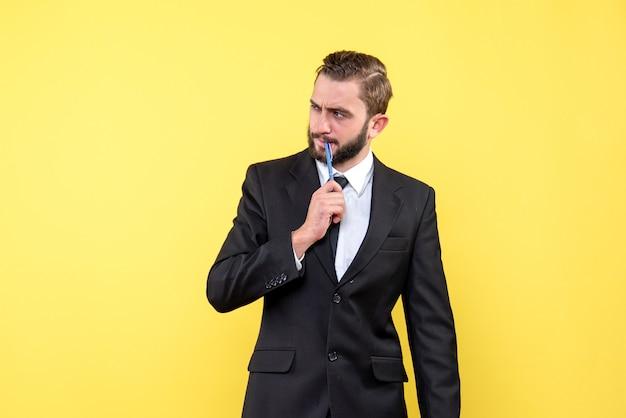 Vista frontale dell'uomo d'affari del giovane che ha un'idea che mette la matita sulla bocca su colore giallo
