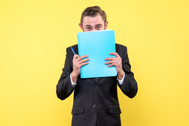 Front view of young man businessman hides the lower part of the face with the blue folder on yellow