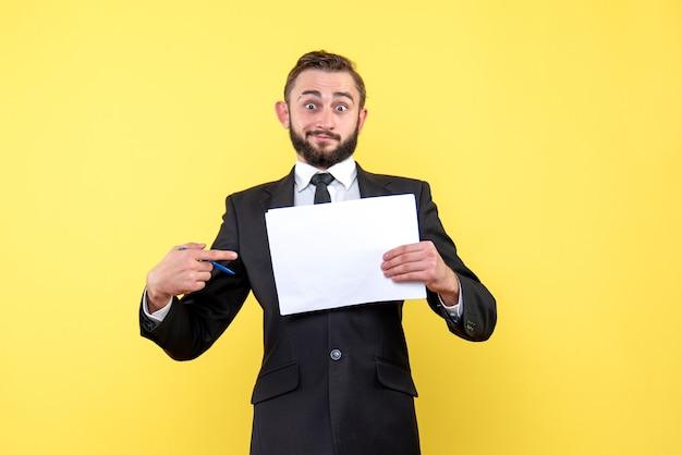 La vista frontale del giovane uomo d'affari sembra sorpreso e punta il dito indice verso un foglio bianco su giallo