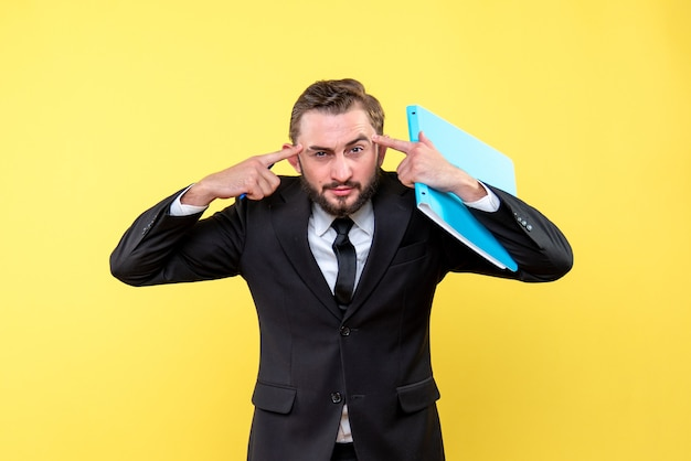 Front view of young man businessman pressing his pointing fingers over forehead bright mind dealing with tasks on yellow