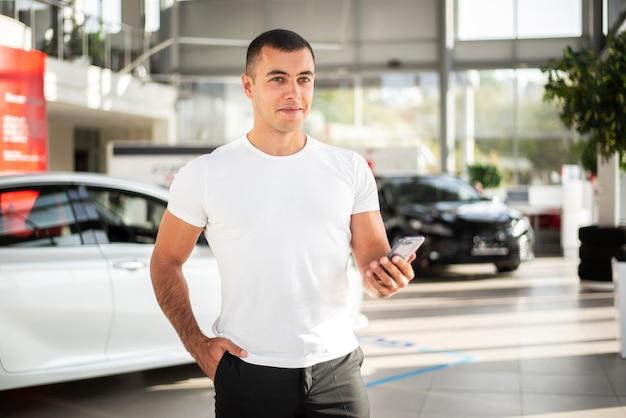 Front view young man at car dealership