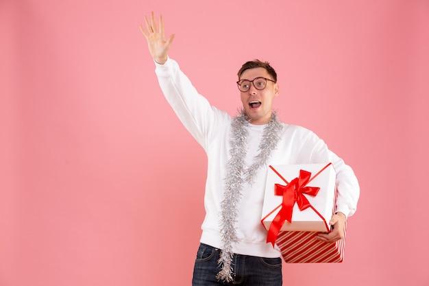 Vista frontale del giovane che porta il regalo di natale sulla parete rosa
