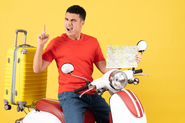 Front view young man in casual clothes on moped holding travel map pointing finger up