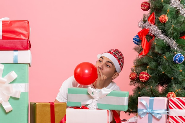 Front view of young man celebrating christmas around presents on a pink wall