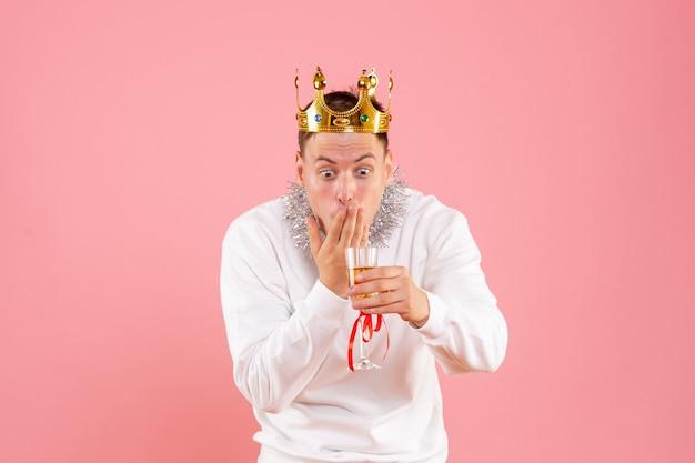 Vista frontale del giovane che celebra il natale con drink scioccato sulla parete rosa
