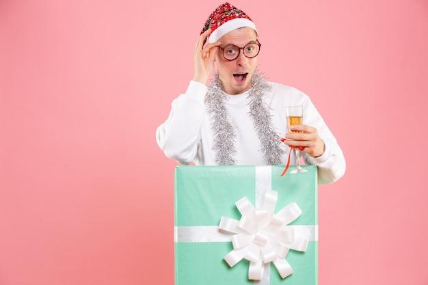 Vista frontale del giovane che celebra il natale con drink e ghirlande su una parete rosa