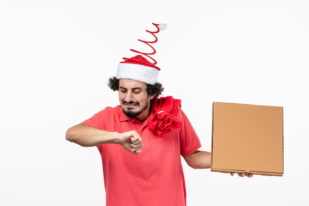 Front view of young man checking time with delivery food box on white wall