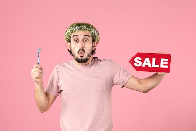 Vista frontale del giovane che si pulisce i denti e tiene in mano un banner di vendita sul muro rosa