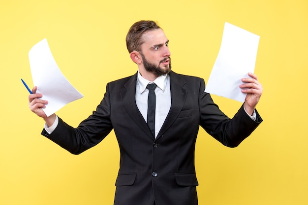 Front view of young man confused businessman in a suit looks indignantly to the blank paper on yellow
