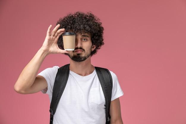 Молодой человек, закрывающий глаза бумажной кофейной чашкой, вид спереди