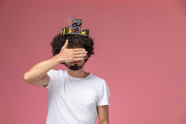 Front view young man covering his eyes with hand and putting his electronic robot on head