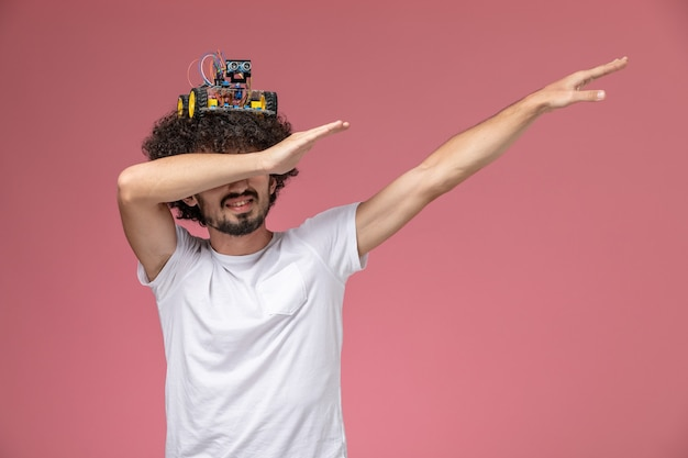 Front view young man dabbing with electronic robot