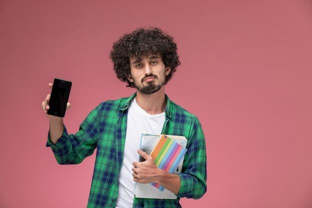 Вид спереди молодой человек демонстрирует свой новый дорогой мобильный телефон